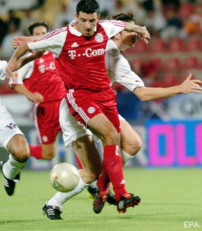 epa00167833 Dutch striker Roy Makaay (C) of Bayern Munich escapes from a tackle by Qatar International All Stars team defender Fabian Sebut during their friendly soccer match at the Al Rayyan Stadium in Doha, Tuesday 06 April 2004.  EPA/-