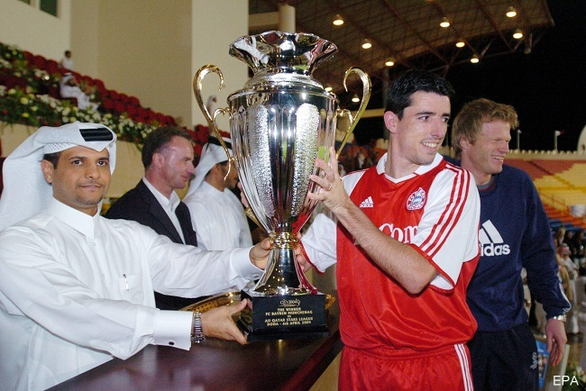 epa00167831 Qatar National Olympic Committee (QNOC) Secretary General Sheikh Saoud bin Abdulrahman al-Thani (L) presents the trophy to Dutch striker Roy Makaay (C) of Bayern Munich after their friendly soccer match against Qatar International All Stars team at the Al Rayyan Stadium in Doha, Tuesday 06 April 2004.  Bayern won 6-5.  EPA/-